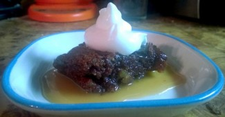 picture of a cooked pudding with whipped cream and sauce in a small plate